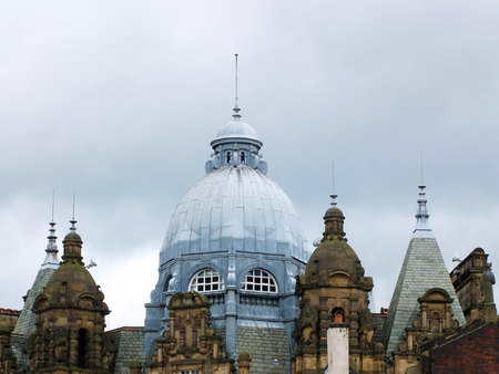 The ornate roof dome and towers of Leeds city market in west Yorkshire against a grey cloudy sky