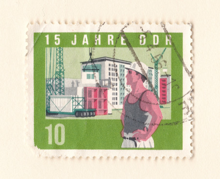 Leeds, England - May 19 2018: An old green east German stamp with an image of a construction worker on a building site with a crane Editorial