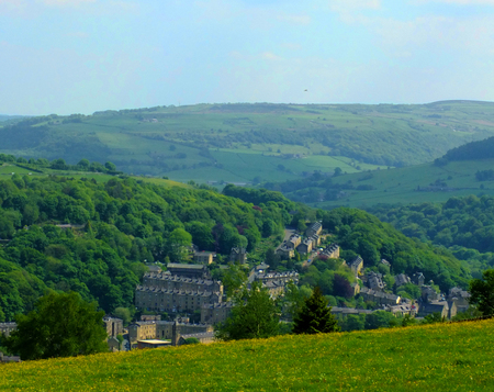 The town of Hebden bridge visible at the bottom of the Calder valley with surrounding Pennine Yorkshire countryside with fields woodland and hills in spring sunlight Stockfoto