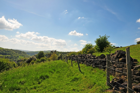 grass path running along a dry stone wall and fence in pennine yorkshire farmland in calderdale with scenic views over the wooded valley and a bright blue spring sky Stock Photo