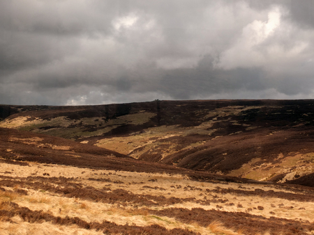 a view of oxenhope moor in west yorkshire with brown dry grass and heather against a grey dramatic cloudy sky