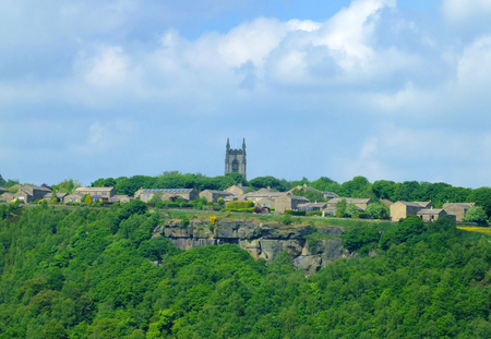 the pennine village of heptonstall viewed from across the calder valley with historic church houses and surrounding woodland and steep rocky hills 写真素材