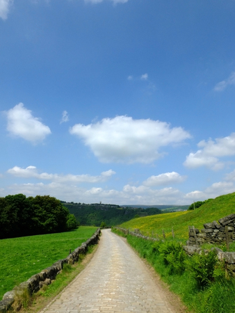long cobbled stone stone road running downhill in beautiful yorkshire dales countryside with green summer meadows with woodland valley in the distance and bright blue sky with clouds