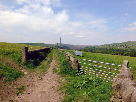 long straight country lane between two stone walls with a gate leading into pastureland in bright summer sunlight with yorkshire pennine hills on the horizon with bright blue summer sky in yorkshire dales countryside