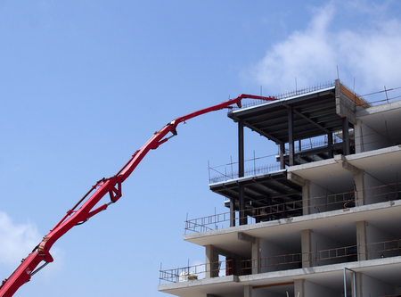 large red articulated crane working on a large modern housing development site with concrete framework and safety barriers with a bright blue sky