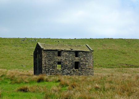 an old abandoned stone farmhouse in green pasture on high pennine moorland with bright blue sky Stock Photo