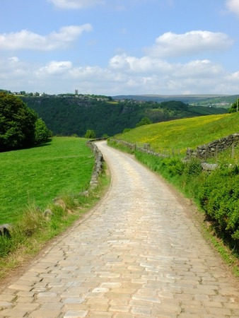 a cobbled country lane curving downhill into the distant wooded valley surrounded by dry stone walls and green fields with a bright blue summer sky with clouds and the yorkshire village of heptonstall visible in the distance