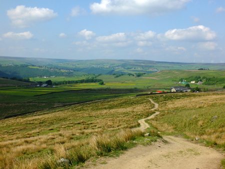 a long winding footpath running downhill in stoodley moor in yorkshire with fields and farms in the distance with the pennine hills on the horizon on a sunny summers day with blue sky and clouds Stock Photo