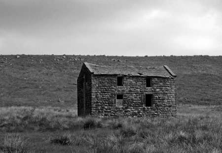 monochrome image of a an old abandoned stone farmhouse in green pasture on high moorland with bright blue sky