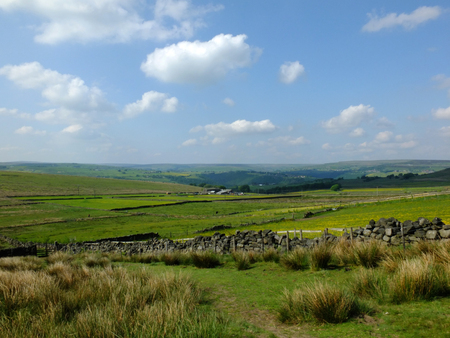 scenic view of a path on the edge of moorland in calderdale west yorkshire with rough tussock grass with dry stone walls bordering pastureland with farmhouses and pennine hills visible in the distance Stock Photo