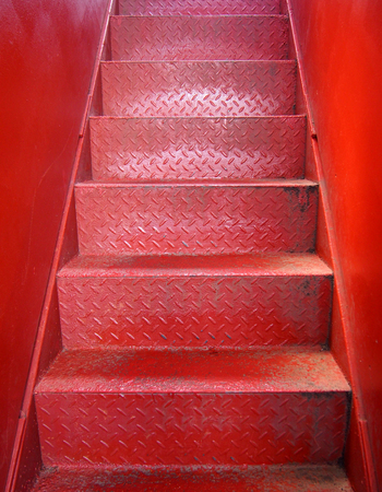 bright red painted metal staircase with steps made of steel plate with a textured surface and smooth pate walls