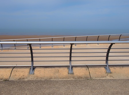 bright modern metal railings along the seaside promenade in blackpool lancashire with concrete sea wall with the ocean and blue summer sky on the horizon