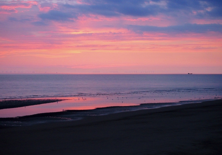 beautiful near dark twilight over a calm flat sea with purple sky and blue clouds reflected in water on the beach