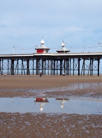 view of a section of the historic victorian south pier in blackpool with the kiosks reflected in the pools on the beach at low tide in summer on a bright sunny day