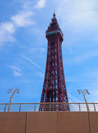 view of blackpool tower looking up from the concrete sea wall with railings and distinctive lamps in summer sunlight with blue sky