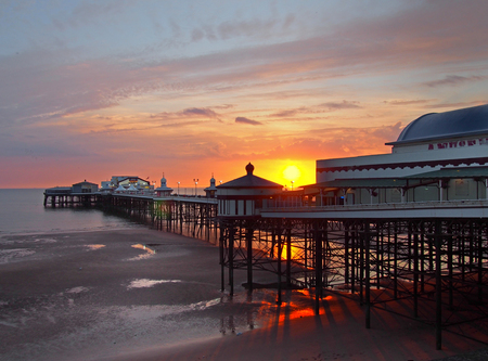 the sun setting over the historic north pier in blackpool with glowing light reflected on the beach and colourful twilight sky