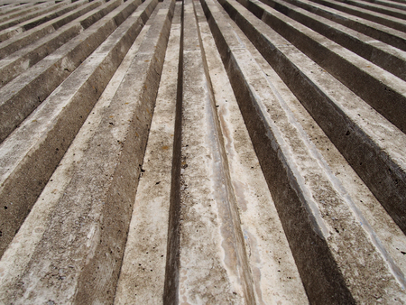 close up of cast concrete with vertical ribbed texture with a converging view in sunlight and shadow