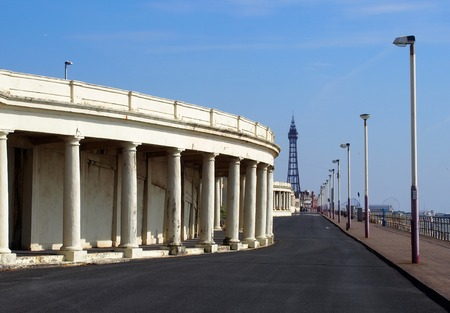 view along the promenade at blackpool showing the pedestrian walkway with old seafront shelters looking towards the pleasure beach and town centre with the tower visible Editorial