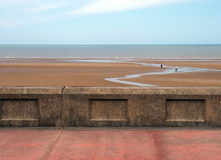 the concrete seawall in blackpool behind the pedestrian walkway with the beach at low tide and calm summer sea with blue sky and clouds