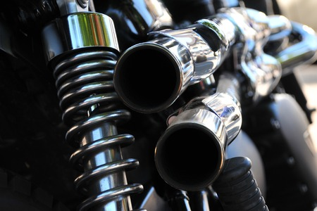 close up rear view of a powerful classic black vintage motorcycle showing suspension and shiny chrome exhaust pipes Stock Photo
