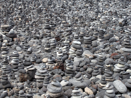 grey pebbles and stones on a beach arranged into a large collection of piles and towers filling the frame