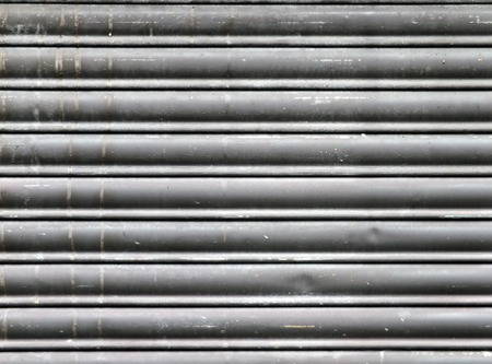 dirty old grey stained horizontal closed steel rolling security shutters Stock Photo
