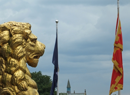 golden lion statues in profile decorating the historic rochdale town hall against a dramatic sky with town flag in the distance Stock Photo