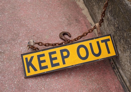 a metal fluorescent yellow keep out sign on a concrete floor with rusty chain attaching it to a wall with an iron hook Stock Photo