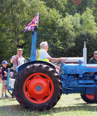 Hebden Bridge, West Yorkshire, England - August 4 2018: a man driving an old british tractor with union jacks at hebden bridge vintage weekend public vehicle show