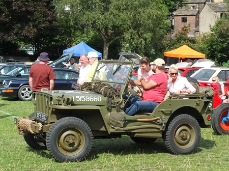 Hebden Bridge, West Yorkshire, England - August 4 2018: A group of people sat in a vintage military jeep and others looking at vintage cars at hebden bridge vintage weekend public vehicle show Editorial
