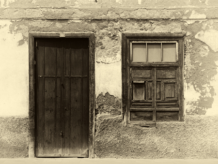 a sepia image of the facade of an old spanish house with shuttered window and old wooden door with faded plaster walls in strong sunlight with shadows