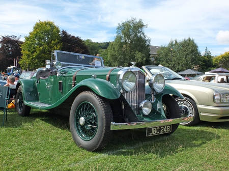 Hebden Bridge, West Yorkshire, England - August 5 2018: an old green vintage bentley open top touring car with people in the background at the Annual Hebden Bridge Vintage Weekend Vehicle Show