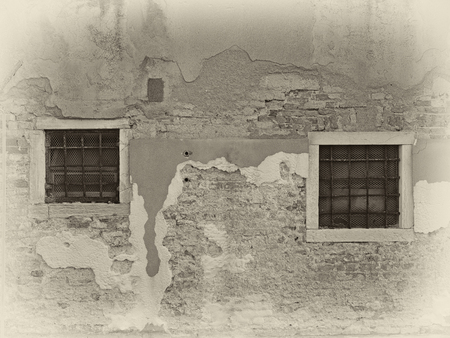 a sepia image of vintage distressed painted wall with two windows bars with white surrounds in bright sunlight and shadow Stock Photo