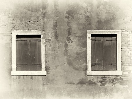 a sepia image of vintage distressed painted wall with two wooden shuttered windows with white surrounds in bright sunlight and shadow