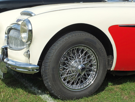 Hebden Bridge, West Yorkshire, England - August 5 2018: the front of a red and white austin healey 3000 sports car showing wheel headlamp and bumper at the Hebden Bridge Vintage Weekend Vehicle Show Editorial