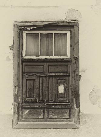a sepia image of an old spanish shuttered window in a traditional house with faded plaster walls in strong sunlight