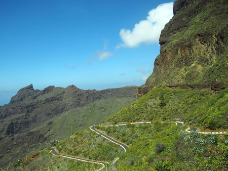 scenic view of high mountain landscape in tenerife with jagged rocky peaks and a narrow road winding down a steep green slope into a valley with blue summer cloudy sky