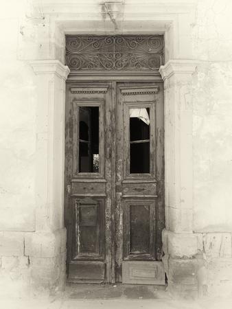 sepia view of a broken old double doors a traditional abandoned spanish house with broken windows and faded peeling paint in a stone frame on a cracked white wall