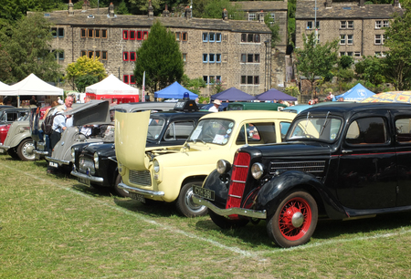 Hebden Bridge, West Yorkshire, England - August 5 2018: people looking at lines of old vlassic cars with bonnets open at hebden bridge vintage weekend public vehicle show