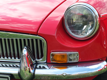 Hebden Bridge, West Yorkshire, England - August 5 2018: front close up of a red british mgb sports car showing headlamp and chrome bumper at the Annual Hebden Bridge Vintage Weekend Vehicle Show Editorial