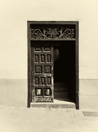 a sepia image of an old wooden door with panels in a traditional spanish house half open revealing stairs inside decorative ironwork and painted walls in bright sunlight and shadow