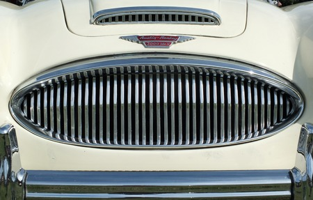 Hebden Bridge, West Yorkshire, England - August 5 2018: close up of the chrome grill bumper and badge of a vintage white austin healey 300 classic sports car at hebden bridge vintage weekend public vehicle show