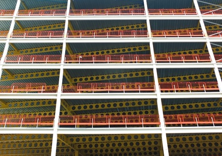 A looking upwards view of large modern commercial building under construction with steel beams and yellow girders with orange safety fences