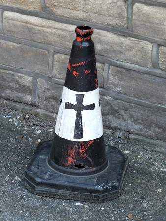 a black painted traffic cone with a religious cross painted on it