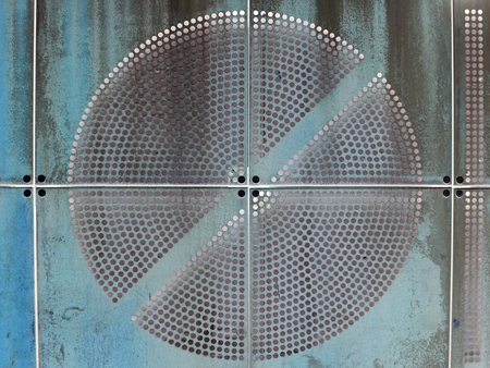blue painted industrial rusty metal plates with round perforated circular pattern Stock Photo