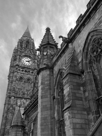 monochrome image of the historic rochdale town hall in lancashire a historic gothic building with tall clock tower ornate stone carvings and gargoyles Stock Photo