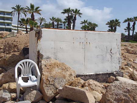 An abandoned white painted concrete bunker in paphos cyprus dating from the civil war era with broken white plastic chair and rocks on the beach next to palm trees and hotels