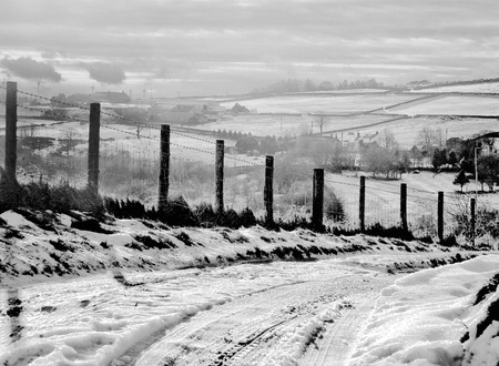 A snow covered rural landscape with a narrow single lane country road with tyre tracks running down a steep hill with a fence alongside with fields and farms on surrounding hills with a grey cloudy sky in the yorkshire dales