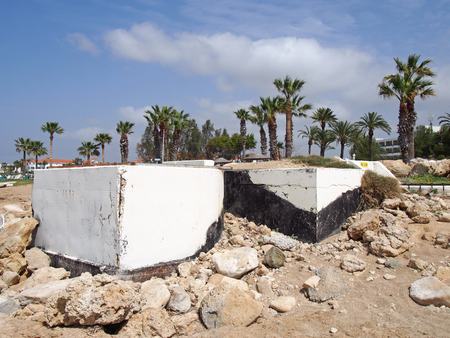 abandoned white painted concrete bunkers in paphos cyprus dating from the civil war era with rocks on the beach next to palm trees and hotels