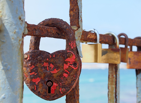 close up of an old heart shaped red rusty padlock chained to a railing with others in a lone out of focus on a bright sunlit summers day 写真素材